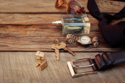 Men accessories: sunglasses, bag,  wrist watch, cufflinks, comb, strap, keys, tie, perfume on the old wood background. Toned image.